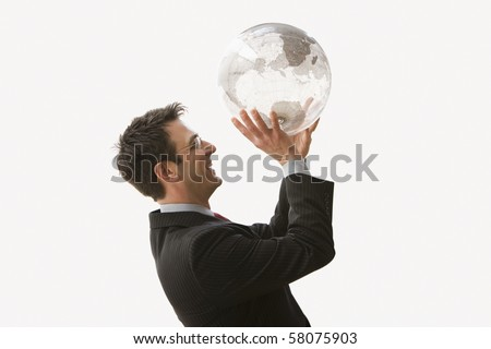 A businessman is smiling and wearing glasses while standing and holding a clear globe like he is shooting a basketball. Horizontal shot. Isolated on white.