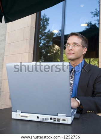 A businessman looking out while surfing the internet from a coffee shop. - stock photo