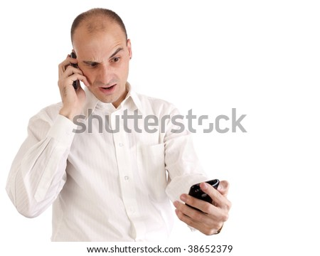 A businessman looks shocked while talking on his cell phone