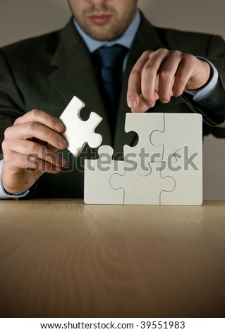 A businessman making a puzzle. - stock photo