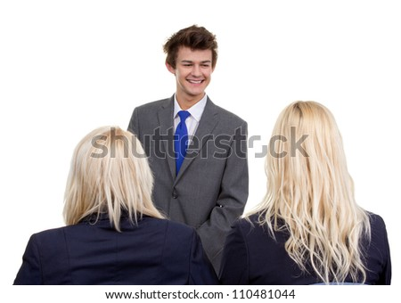A businessman man relaxed standing infront of two business women, isolated on white