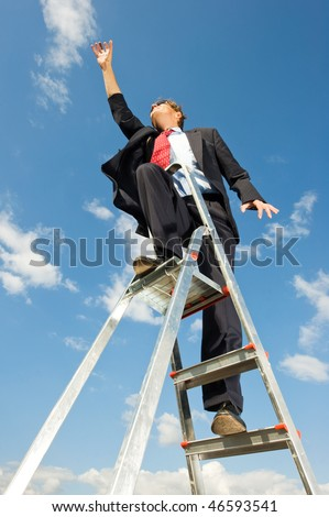 A businessman on a ladder reaching for the sky as if the limit is beyond the sky.