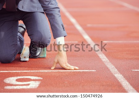 A businessman on a track ready to run