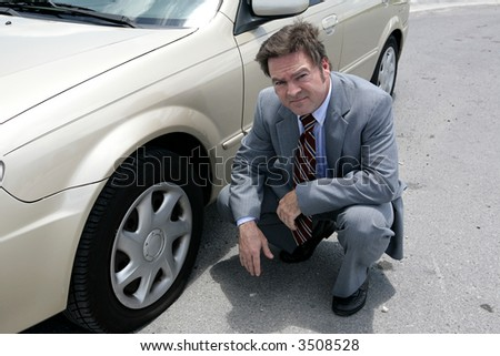 A businessman on the road with a flat tire.  He looks upset.