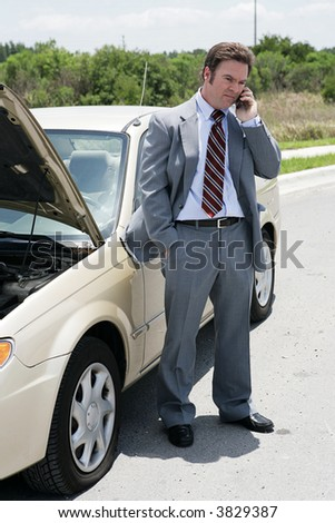 A businessman on the road with a flat tire.  He's calling his next appointment to say he will be late.