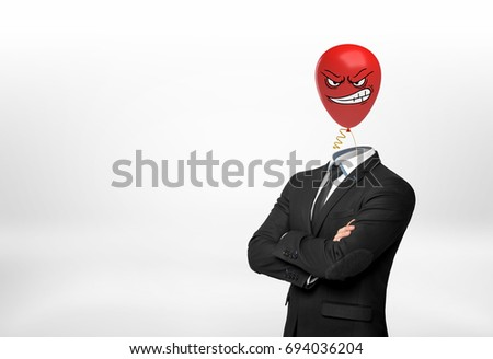 A businessman on white background stands with crossed hands and a red angry face balloon instead of his head. Aggressive leadership. Workplace conflict. Corporate intolerance. Photo stock ©