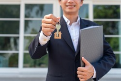 A businessman or home sales agent is happily handing the house keys to a new landlord. New house move ideas, home leasing and selling home.