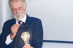 a businessman or scientist show bulb lighting was holding in hand as idea or creative concept