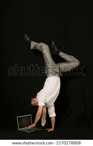 A businessman performs a one armed handstand, typing on a laptop