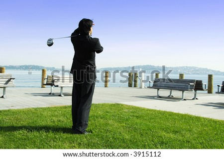 A businessman playing golf during his business break