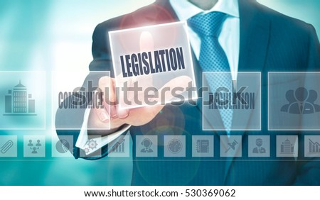 A businessman pressing a Legislation button on a transparent screen.