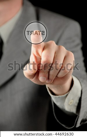 A businessman pressing a virtual start button against a black background