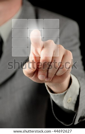 A businessman pressing one of twelve virtual buttons against a black background