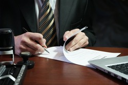 A businessman puts his signature on the contract