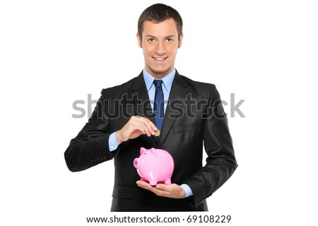 A businessman putting a coin into a piggy bank isolated on white background