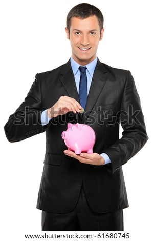 A businessman putting a coin into a pink piggy bank isolated on white background