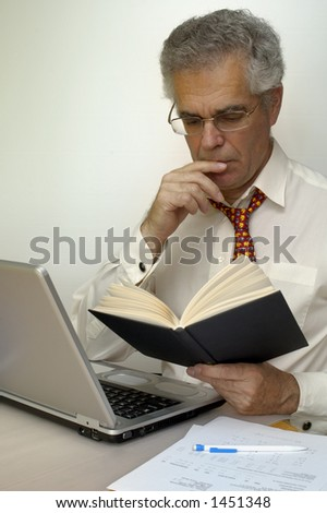 A businessman reads a book as he sits at his laptop.. Space for text on the white background.