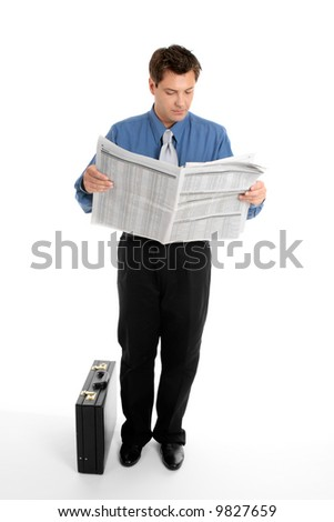 A businessman reads the finance newspaper while waiting for bus, train, taxi.  Newsprint has been blurred.