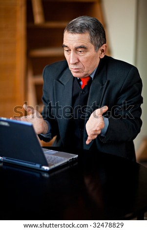 A businessman recoils from his laptop computer in horror.
