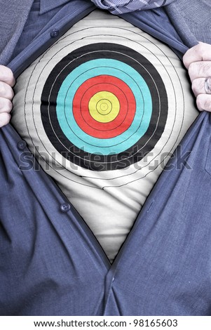 A businessman rips open his shirt and shows how perfect he is for your needs by showing off a target printed on a t-shirt