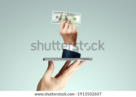 A businessman's hand crawls out of the smartphone screen with a one hundred dollar bill. Concept of money transfers, internet banking work online