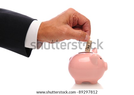 A businessman's hand putting a small one hundred dollar bill into a piggy bank. Horizontal over a white background with reflection under bank.