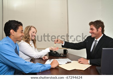 A businessman/salesman/realtor hands over the house keys to a couple after buying their house/closing the sale