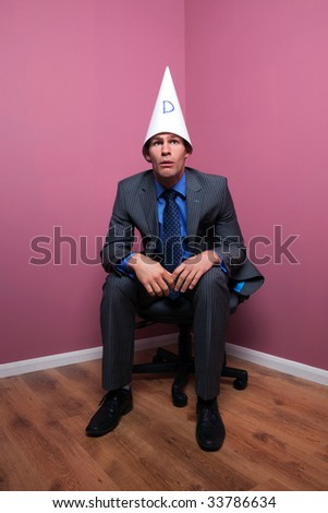 A businessman sat in the corner of the room wearing a dunce's hat with a dumb expression on his face.