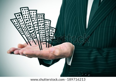 a businessman showing a pile of drawn buildings in his hands Stock fotó ©
