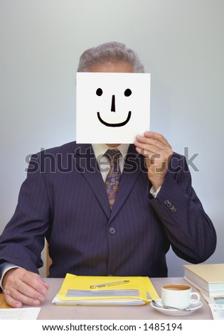 A businessman sits at his desk, holding a home-made smiley mask in front of his face. Look ... I'm happy ... really!