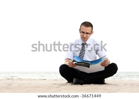 a businessman sitting and reading newspaper near the sea