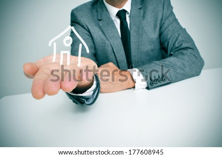 a businessman sitting in a desk showing a drawing of a house in his hand Stock fotó ©