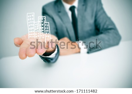 a businessman sitting in a desk showing a pile of drawn buildings in his hand Stock fotó ©