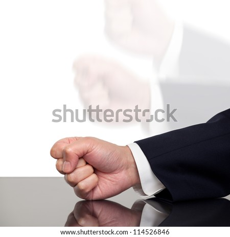 A businessman slamming his fist on a table