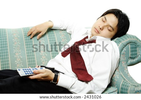 A businessman sleeping on a couch holding a TV remote