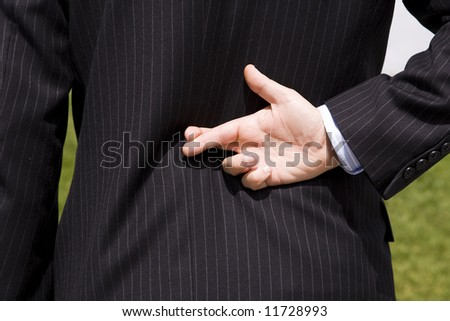 a businessman telling a lie with the fingers crossed