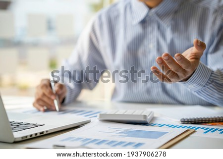 A businessman that operates on the table being checking data, Concept financial transactions online of a businessman, Financier being check about financial transaction past computer with teamwork.
