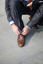 A businessman tying his shoelaces