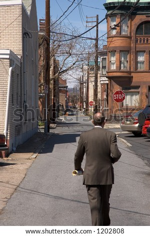 Businessman walking down the back street of a dirty city stock