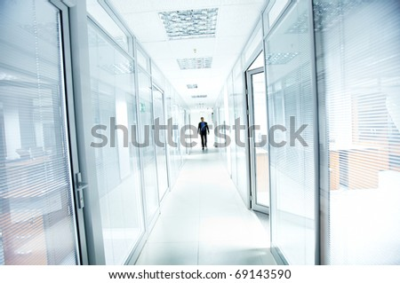 A businessman walking in the office corridor - stock photo