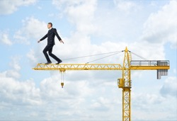 A businessman walking on the yellow construction crane, trying to balance himself and get to the end of the jib, on the sky background. Business difficulties and risks. Overcoming obstacles