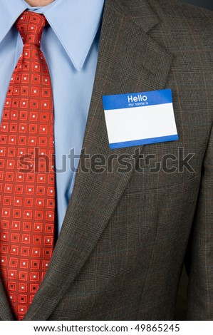 A businessman wearing a blank name tag and a sharp business suit.