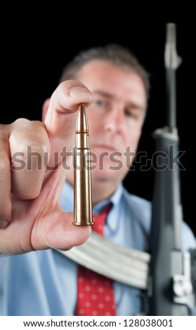 A businessman wearing a dress shirt and necktie shows off a large 223 bullet for his assault rifle.