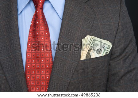 A businessman wearing a suit and tie with cash sticking out of his pocket.