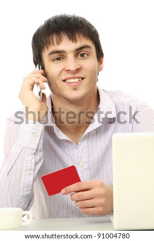 A businessman with a credit card, laptop sitting at the desk and talking on phone , isolated on white background