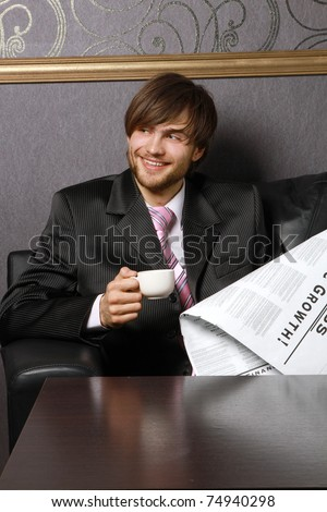 A businessman with a cup of coffee and a newspaper