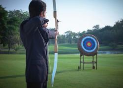 A businessman with an arrow to shoot at the target for success