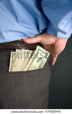 A businessman with cash sticking out of back pocket.