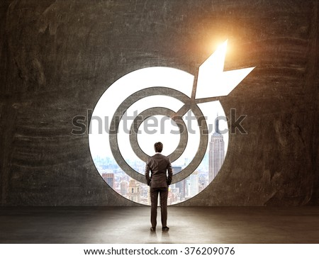 A businessman with hands in pockeys standing in front of a target through which he can see New York. Back view. Black background. Concept of achieving a goal.