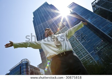 A businessman with his arms out stretched 'messiah like' in a modern city environment with the sun bursting over glass fronted office buildings behind him